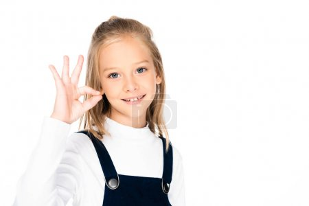Photo for Adorable, smiling schoolgirl showing ok gesture while looking at camera isolated on white - Royalty Free Image