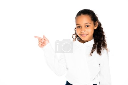 adorable african american schoolgirl pointing with finger while looking at camera isolated on white
