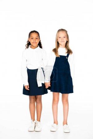 Photo pour Vue pleine longueur de deux écolières multiculturelles tenant la main sur fond blanc - image libre de droit