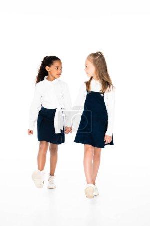 Photo pour Vue pleine longueur de deux écolières multiculturelles tenant la main et marchant ensemble sur fond blanc - image libre de droit