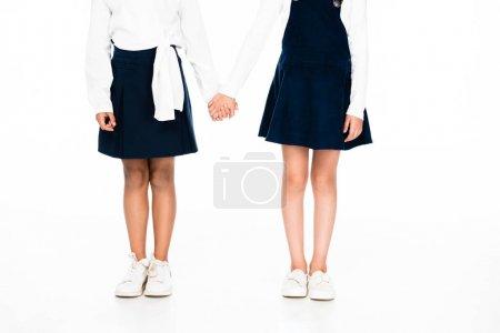 Photo pour Vue recadrée de deux écolières multiculturelles tenant la main sur fond blanc - image libre de droit