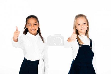 Photo pour Deux écolières multiculturelles souriantes montrant pouces vers le haut tout en regardant la caméra isolée sur blanc - image libre de droit