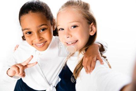 Photo pour Foyer sélectif de l'écolière américaine africaine gaie affichant le signe de victoire tout en étreignant l'ami d'isolement sur le blanc - image libre de droit