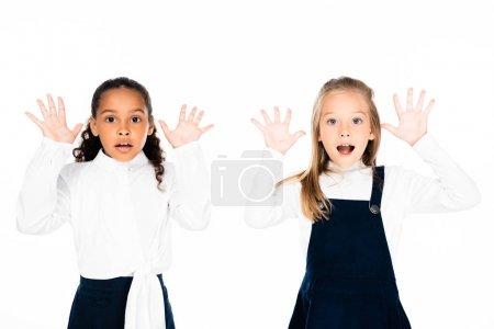 Foto de Dos escolares multiculturales sorprendidos mostrando tiza manchada manos aisladas en blanco - Imagen libre de derechos
