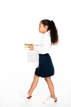 Photo pour Vue latérale de l'adorable écolière afro-américaine marchant tout en tenant des livres sur fond blanc - image libre de droit