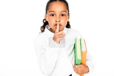 Photo pour Cute african american schoolgirl showing hush gesture while holding books isolated on white - image libre de droit
