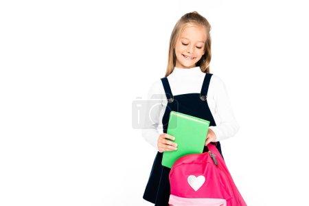 Photo pour Écolière adorable souriant tout en mettant le livre dans le sac à dos d'isolement sur le blanc - image libre de droit