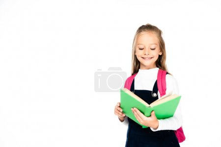 Photo for Adorable schoolgirl smiling while reading books isolated on white - Royalty Free Image