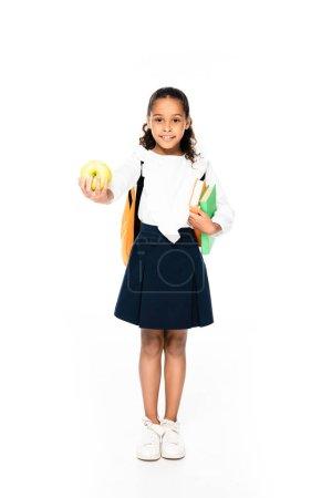Photo pour Vue pleine longueur de l'adorable écolière afro-américaine souriant à la caméra tout en tenant des livres et de la pomme sur fond blanc - image libre de droit