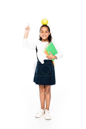 Photo pour Vue pleine longueur de l'écolière afro-américaine avec pomme sur la tête tenant des livres et montrant geste d'idée sur fond blanc - image libre de droit