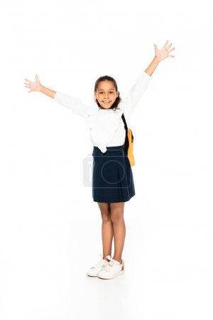 Photo for Full length view of cheerful african american schoolgirl gesturing with raised hands on white background - Royalty Free Image