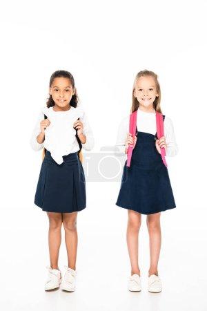 Photo pour Vue pleine longueur de deux adorables écolières multiculturelles souriant à la caméra sur fond blanc - image libre de droit