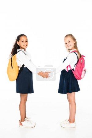 Photo pour Vue pleine longueur de deux écolières multiculturelles mignonnes tenant la main et regardant la caméra sur fond blanc - image libre de droit