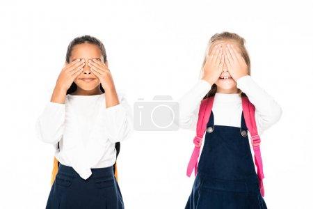 Photo pour Deux écolières multiculturelles couvrant les visages avec les mains isolées sur blanc - image libre de droit