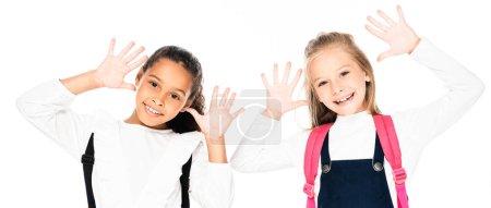 Foto de Foto panorámica de dos colegialas multiculturales alegres mostrando las manos manchadas de tiza aisladas en blanco - Imagen libre de derechos