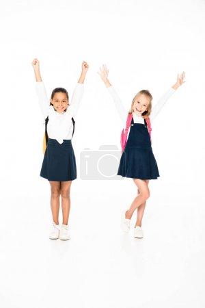 Photo pour Vue pleine longueur de deux écolières multiculturelles heureux montrant des gestes oui sur fond blanc - image libre de droit