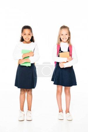 Photo pour Vue pleine longueur de deux adorables écolières multiculturelles tenant des livres sur fond blanc - image libre de droit