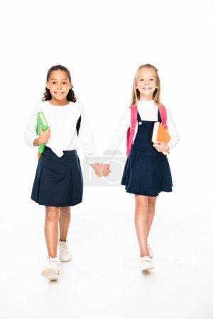 Photo pour Vue pleine longueur de deux écolières multiculturelles souriantes marchant tout en se tenant la main sur fond blanc - image libre de droit