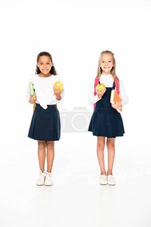 Photo pour Vue pleine longueur de deux écolières multiculturelles souriantes tenant des livres et des pommes sur fond blanc - image libre de droit