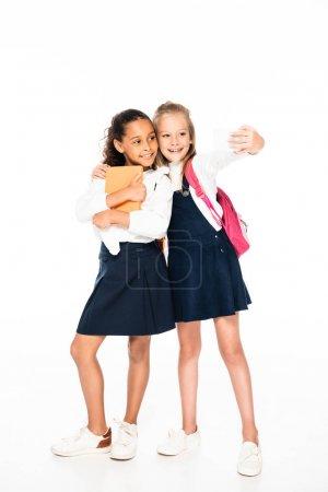 Photo pour Vue pleine longueur de heureuse écolière étreignant un ami afro-américain et prenant selfie sur fond blanc - image libre de droit