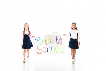 Photo for Full length view of two multicultural schoolgirls holding placard with back to school inscription while walking on white background - Royalty Free Image