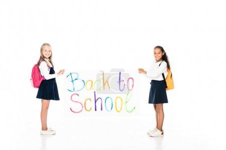 Photo pour Vue pleine longueur de deux écolières multiculturelles avec sacs à dos portant une pancarte avec inscription de retour à l'école sur fond blanc - image libre de droit
