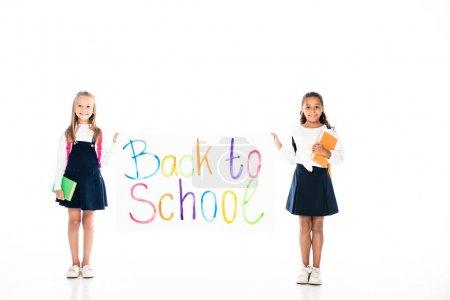 Photo pour Vue complète de deux écolières multiculturelles tenant des livres et une pancarte avec inscription de retour à l'école sur fond blanc - image libre de droit