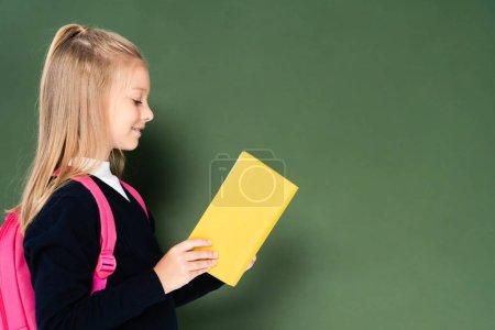 Photo pour Vue latérale du livre de lecture d'écolière souriante tout en se tenant près du tableau vert - image libre de droit