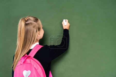 Photo for Back view of schoolgirl with pink backpack writing on green chalkboard - Royalty Free Image