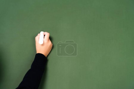 Photo for Cropped view of schoolgirl writing with chalk on green chalkboard - Royalty Free Image