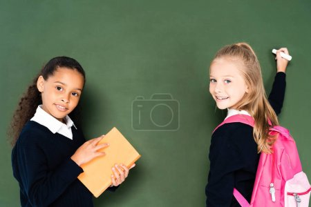 Photo pour Écolière afro-américaine retenant le livre près de camarade de classe avec le morceau de craie près du tableau vert - image libre de droit