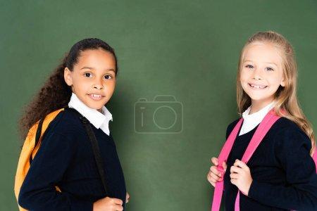 Photo pour Deux écolières miltucultural souriantes souriant à l'appareil-photo tout en restant près du tableau vert - image libre de droit