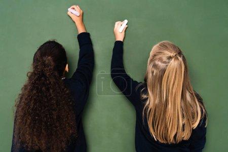 Photo pour Vue arrière de deux écolières multiculturelles écrivant sur un tableau à craies - image libre de droit