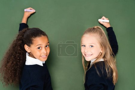 Photo for Two cheerful multicultural schoolgirls smiling at camera while writing on chalkboard - Royalty Free Image