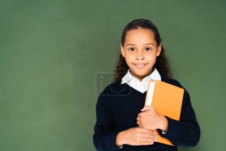 Photo for Adorable african american schoolgirl holding book and looking at camera while standing near green chalkboard - Royalty Free Image