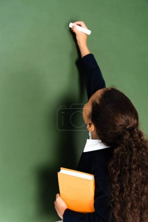Photo for Back view of african american schoolgirl writing on chalkboard while holding book - Royalty Free Image
