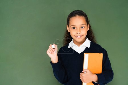 Photo for Cheerful african american schoolgirl holding piece of chalk and book while standing near chalkboard - Royalty Free Image