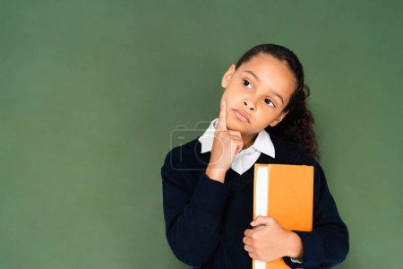Photo for Thoughtful african ameican schoolgirl holding book and looking away while standing near chalkboard - Royalty Free Image