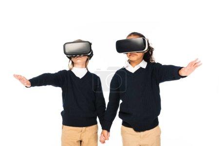 Foto de Dos colegialas multiculturales que se toman de la mano mientras usan auriculares de realidad virtual aislados en blanco - Imagen libre de derechos