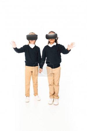 Photo pour Vue pleine longueur de deux écolières multiculturelles retenant des mains tout en utilisant des casques virtiaux de réalité sur le fond blanc - image libre de droit