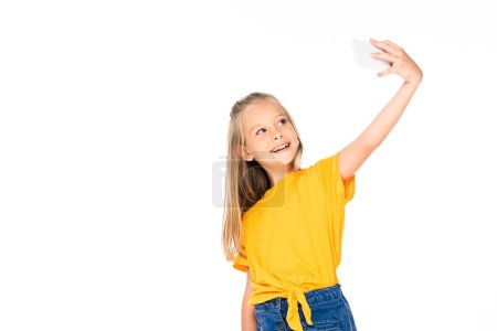 Photo for Happy kid smiling while taking selfie with smartphone isolated on white - Royalty Free Image