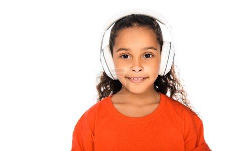 Photo pour Adorable enfant afro-américain souriant à la caméra tout en écoutant de la musique dans des écouteurs isolés sur blanc - image libre de droit