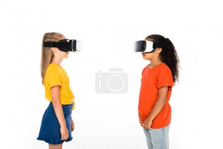 Photo for Two multicultural friends looking at each other while using virtual reality headsets isolated on white - Royalty Free Image