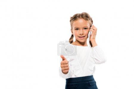 Photo pour Gosse heureux affichant le pouce vers le haut tout en parlant sur le smartphone d'isolement sur le blanc - image libre de droit
