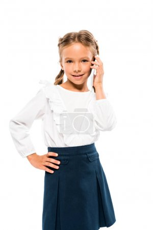 Photo for Cute kid standing with hand on hip and talking on smartphone isolated on white - Royalty Free Image