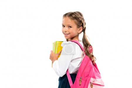 smiling child standing with pink backpack and books isolated on white