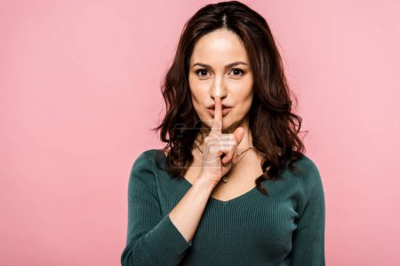 attractive woman showing hush sign isolated on pink