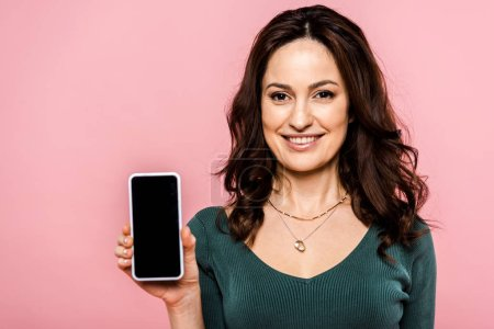 happy woman holding smartphone with blank screen isolated on pink