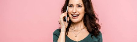 Photo for Panoramic shot of happy woman talking on smartphone isolated on pink - Royalty Free Image