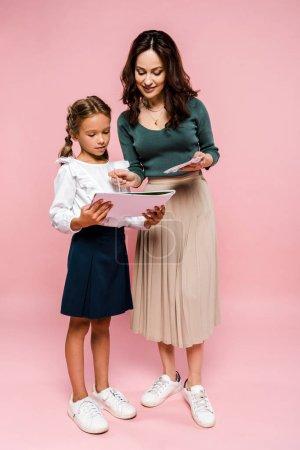 Photo pour Mère heureuse debout près de fille et peinture sur rose - image libre de droit